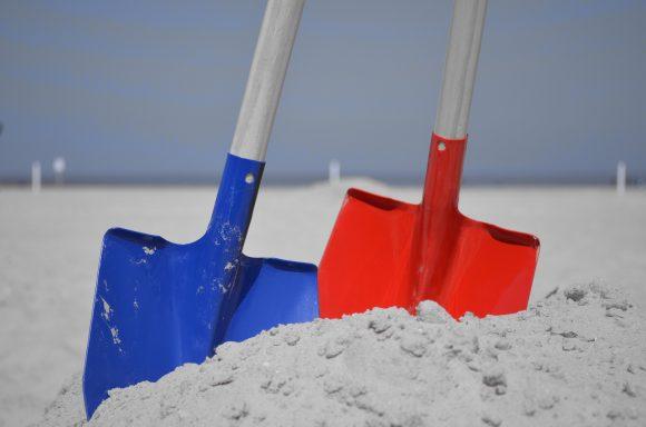 Pelles rouge et bleue dans le sable